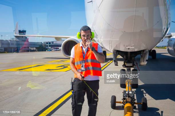 ground crew towing airplane to the runway for departure - airfield stock pictures, royalty-free photos & images
