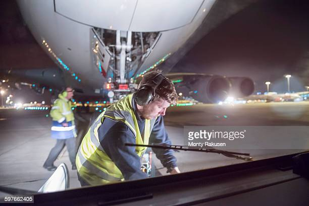 Ground crew uncoupling tug A380 aircraft on runway at night