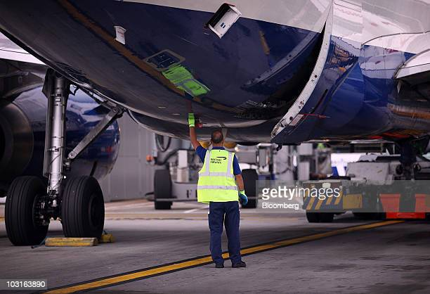 A ground crew worker examines a British Airways aircraft at Heathrow airport in London UK on Thursday July 29 2010 British Airways Plc said its...