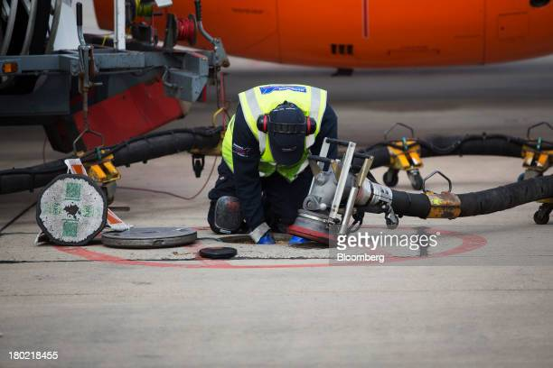 A ground crew worker prepares to attach an aircraft fuel pipe to an underground storage tank at Stansted Airport operated by Manchester Airports...