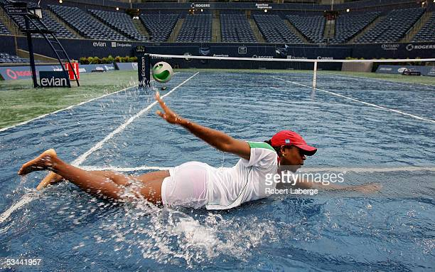 Ground crew worker Rachel Oryena pretends to swim in the water on center court after torrential rains delayed the game between Amelie Mauresmo of...
