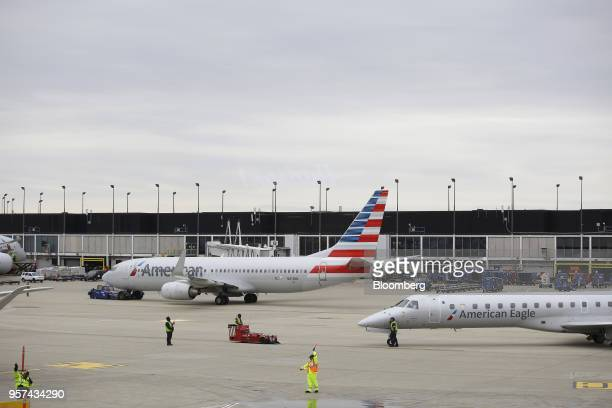 Ground crew workers direct an American Airlines Group Inc plane on the tarmc during an event to mark the opening of five new gates inside Terminal 3...