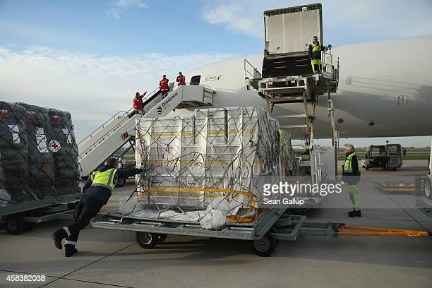 Ground crew workers load a plane with a 25ton shipment of tents generators airconditioning units chlorine for disinfection and other supplies from...