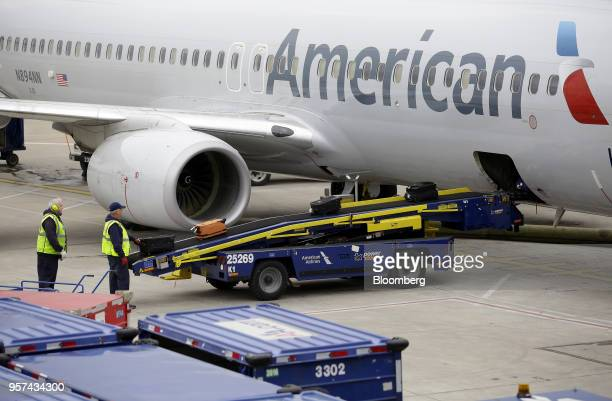 Ground crew workers load luggage onto an American Airlines Group Inc plane during an event to mark the opening of five new gates inside Terminal 3 at...