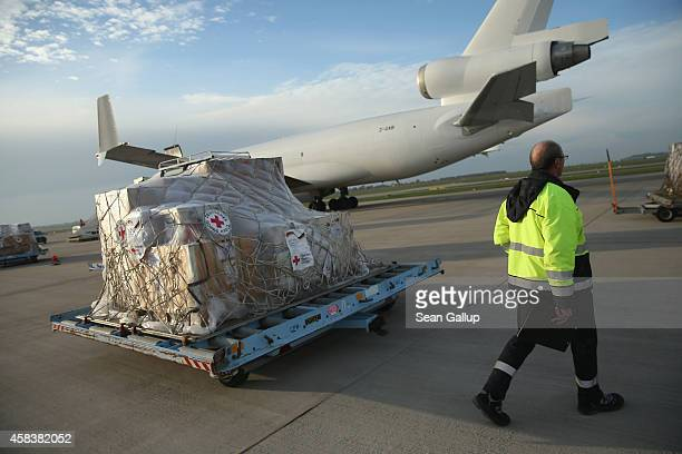 Ground crew workers prepare to load a plane with a 25ton shipment of tents generators airconditioning units chlorine for disinfection and other...