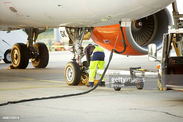 Ground crew working below a passenger airplane and refueling