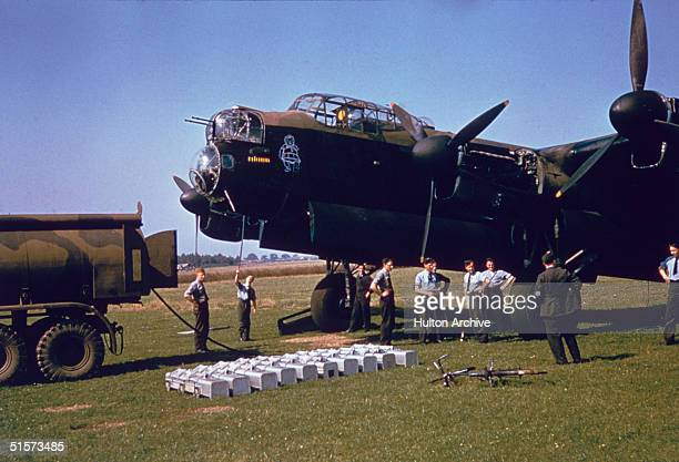 Ground crews loading and refueling an Avro Lancaster heavy bomber circa 1943