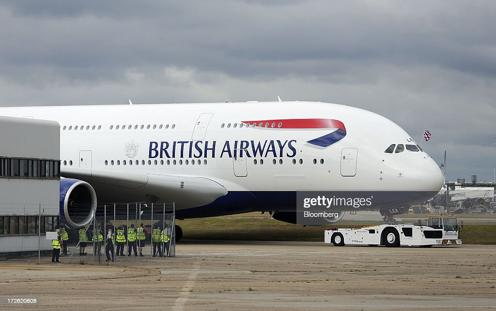 Ground crews watch as a new Airbus A380 aircraft operated by British Airways (BA) is pulled along the tarmac by a tractor after landing at Heathrow airport in London, U.K., on Thursday, July 4, 2013. British Airways will start regular services with the Airbus SAS A380 superjumbo a week earlier than planned after taking delivery of the first of 12 of the doubledeckers today. Photographer: Chris Ratcliffe/Bloomberg via Getty Images