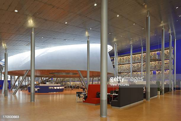 Ground floor with suspended bookcase against blue wall metallic columns and cone with daylight TU Delft Library Delft Netherlands Architect Mecanoo...