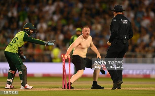 Ground intruder knocks off the bails watched by Mohammad Rizwan of Pakistan and umpire David Millns during the 3rd Vitality T20 International between...