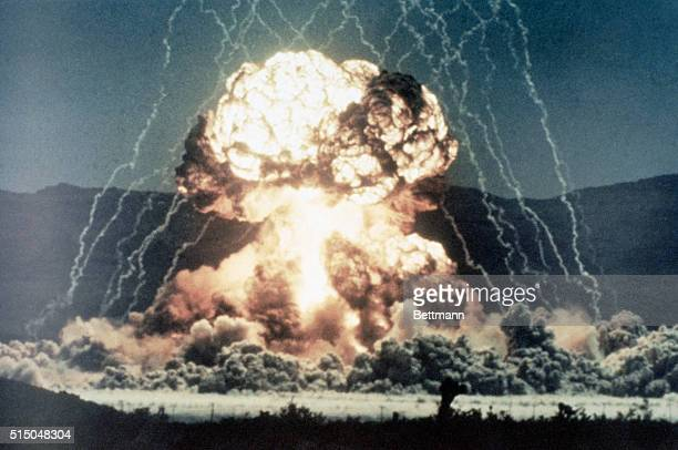 Ground level view of a surface test of a nuclear device Slide shows the beginning of a mushroom cloud glowing intensly white with lightning arcing...