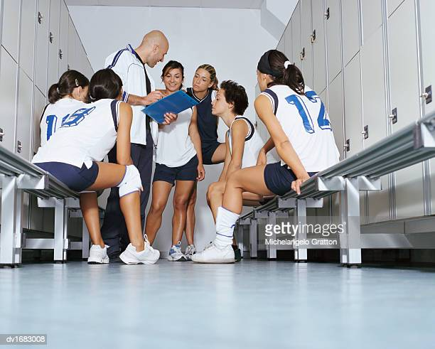 Ground Level View of a Volleyball Team Listening to Their Coach in a Changing Room