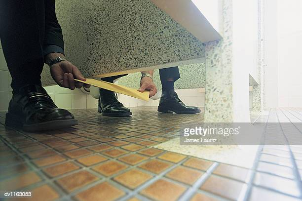 Ground Level View of Businessmen Passing An Envelope in a Public Lavatory