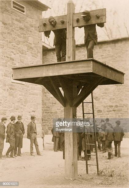 Ground level whipping post above which is a platform for the pillory presently occupied by two African American men a ladder leans against the...