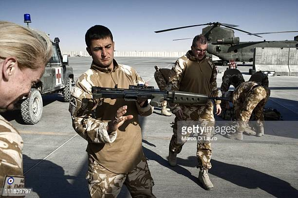 Ground medic SAC Caspar Coole, 32-years-old from the RAF Lyneham Medical Center checks his rifle at the flight line in Camp Bastion on November 23,...