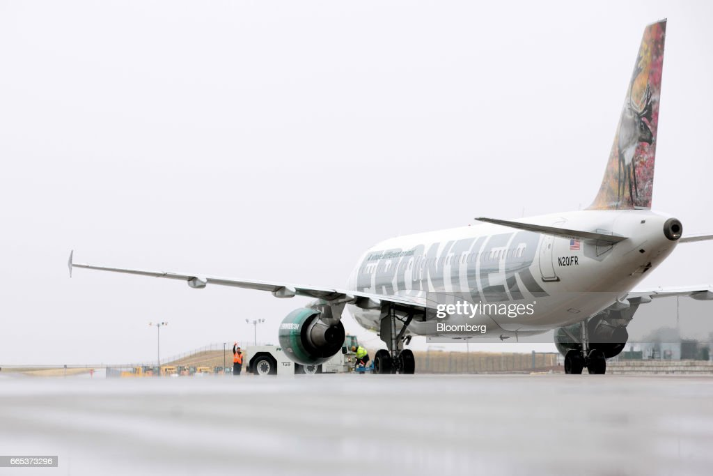 A ground operations employee directs a Frontier Airlines Inc