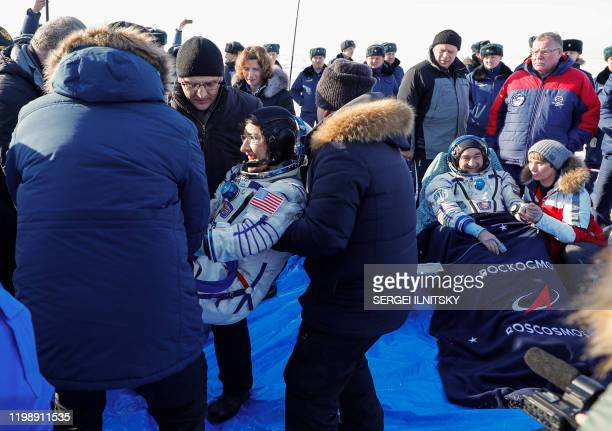 Ground personnel carry NASA astronaut Christina Koch as Russian cosmonaut Alexander Skvortsov rests in a chair shortly after landing in a remote area...