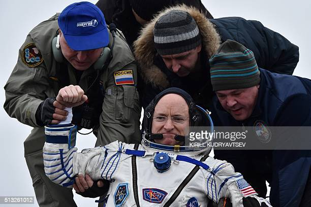 Ground personnel help International Space Station crew member Scott Kelly of the US to get out of the Soyuz TMA18M space capsule after landing near...