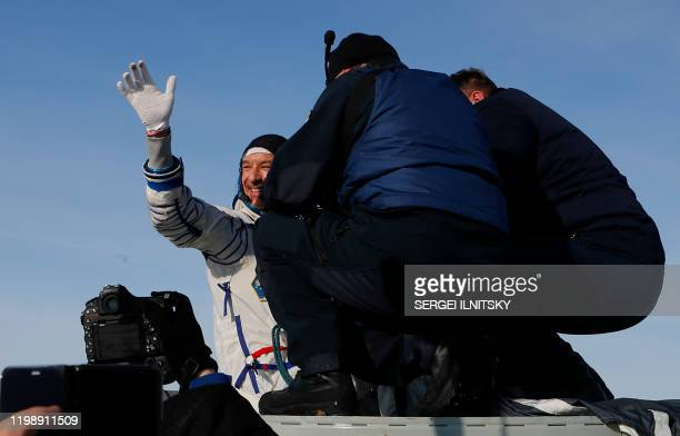 Ground personnel help Luca Parmitano of the European Space Agency to get out of the Soyuz MS13 capsule shortly after landing in a remote area outside...