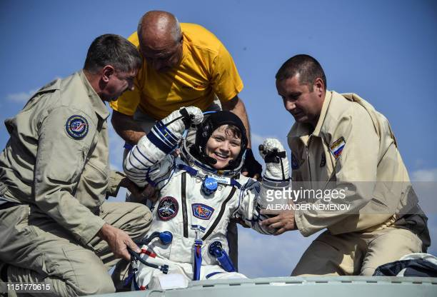 Ground personnel help NASA astronaut Anne McClain to get out of the Soyuz MS11 capsule shortly after landing in a remote area outside the town of...