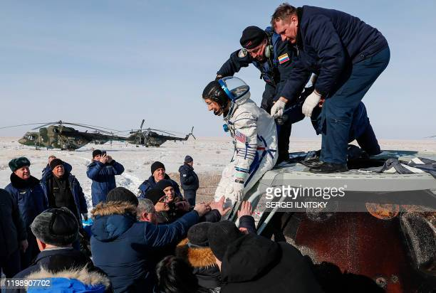 Ground personnel help NASA astronaut Christina Koch to get out of the Soyuz MS13 capsule shortly after landing in a remote area outside the town of...
