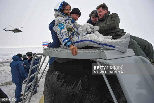 TOPSHOT Ground personnel help NASA astronaut Joe Acaba to get out of the Soyuz MS06 space capsule after landing in a remote area outside the town of...