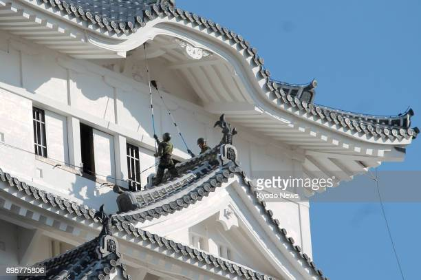 Ground SelfDefense Force members on Dec 20 sweep the soot off Himeji Castle a hilltop castle complex located in Himeji Hyogo Prefecture western Japan...