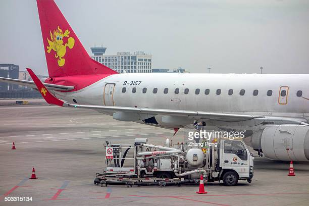 Ground service men are checking a passenger plane on tarmac A passenger plane of Air China stops on tarmac The year of 2015 is the most profitable...