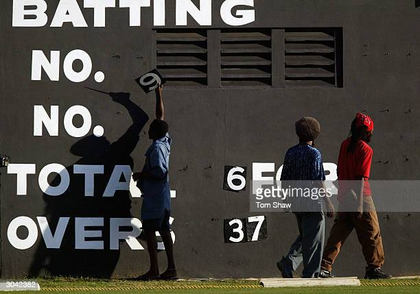 Ground staff adjust the scoreboard during day 3 of the Jamaica v England 3 day warm up match at Sabina Park Cricket ground, on March 3 in Kingston,...