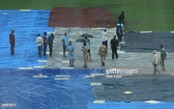Ground staff assess the covers over the playing square under heavy rain before the seventh one day international match between Australia and India at...