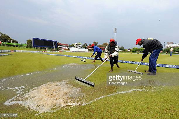 Ground staff attempt to clear rain water from the pitch during day three of the first test match between South Africa and Bangladesh held at the...
