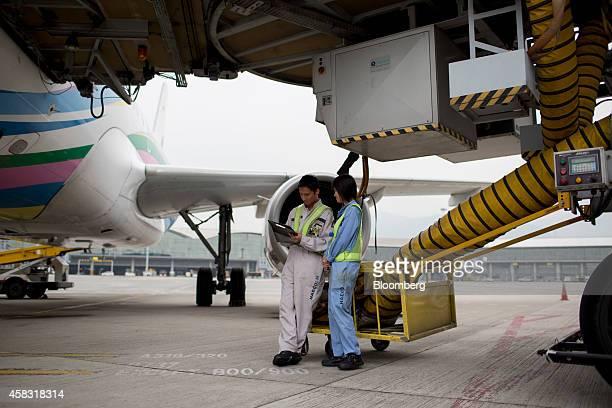 Ground staff chat beside a Bangkok Airways Co Airbus SAS A319 aircraft at Hong Kong International Airport in Hong Kong China on Monday Nov 3 2014...