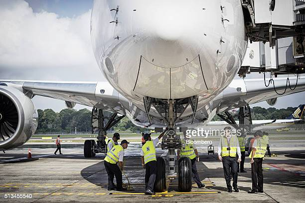 Ground staff check an Airbus SE A350 aircraft operated by Singapore Airlines Ltd during an arrival ceremony at Changi Airport in Singapore on...