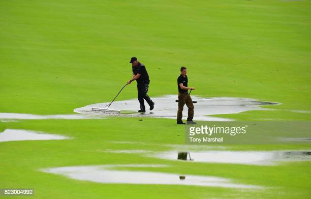 Ground staff clear the surface water on the 18th fairway after heavy overnight rain during the Porsche European Open Pro Am at Green Eagle Golf...