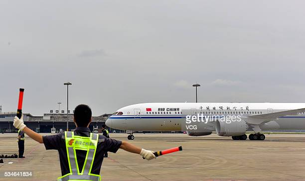 Ground staff commands the aircraft into the specified location at Chengdu Shuangliu International Airport on May 26, 2016 in Chengdu, Sichuan...