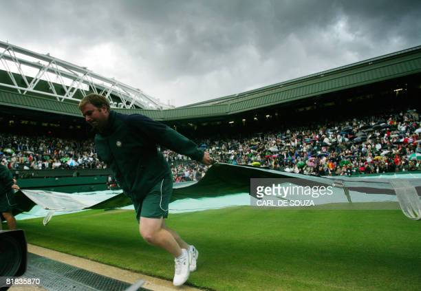 Ground staff cover the court due to the rain during the final tennis match of the 2008 Wimbledon championships between Switzerland's Roger Federer...