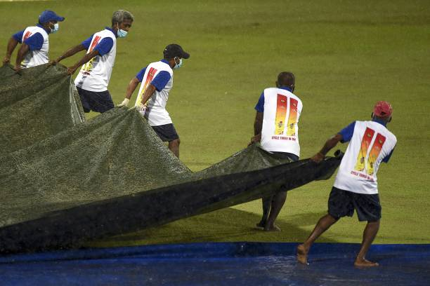 Ground staff cover the cricket pitch as rain stops play during the second international Twenty20 cricket match between Sri Lanka and South Africa at...