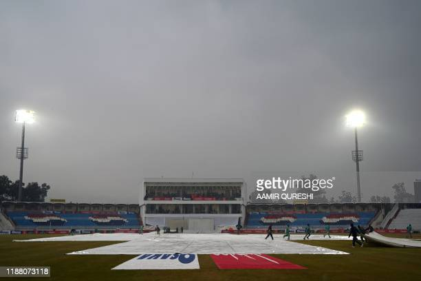 Ground staff cover the pitch during rain showers on the second day of the first Test cricket match between Pakistan and Sri Lanka at the Rawalpindi...
