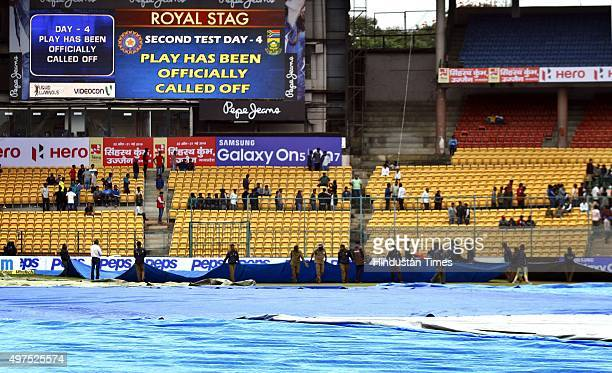 Ground staff covering the ground as rain continues during the 2nd Test match between India and South Africa at M Chinnaswamy Stadium on November 17...