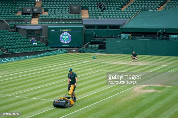 Ground Staff cutt the grass on Centre Court ahead of the day's play on the fifth day of the 2021 Wimbledon Championships at The All England Tennis...