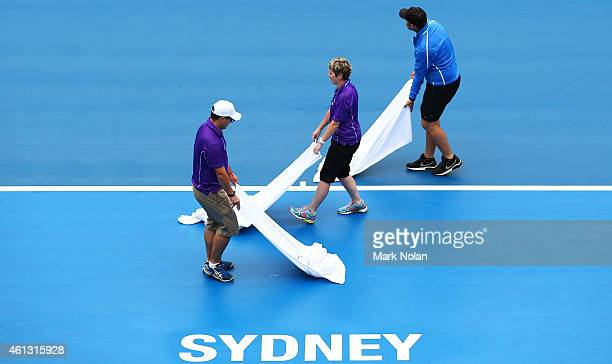Ground staff dry the courts after persistent rain during the day one of the 2015 Sydney International at Sydney Olympic Park Tennis Centre on January...