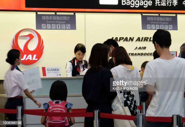 Ground staff for Japan Airlines work at a counter at Tokyo's Haneda airport on July 31 2018 Major Japanese carriers All Nippon Airways and Japan...