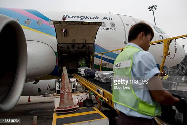 Ground staff handle luggage beside a Bangkok Airways Co Airbus SAS A319 aircraft at Hong Kong International Airport in Hong Kong China on Monday Nov...