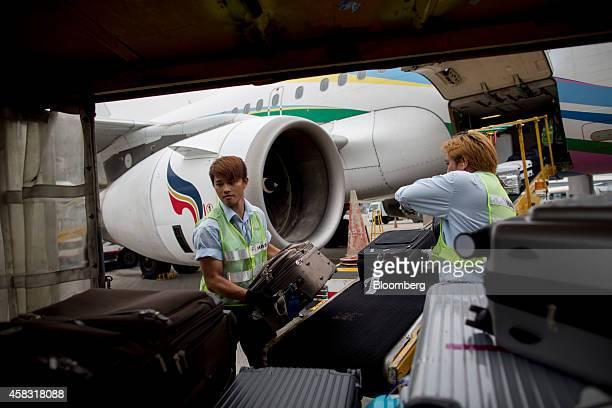 Ground staff load luggage on to a cart near a Bangkok Airways Co Airbus SAS A319 aircraft at Hong Kong International Airport in Hong Kong China on...
