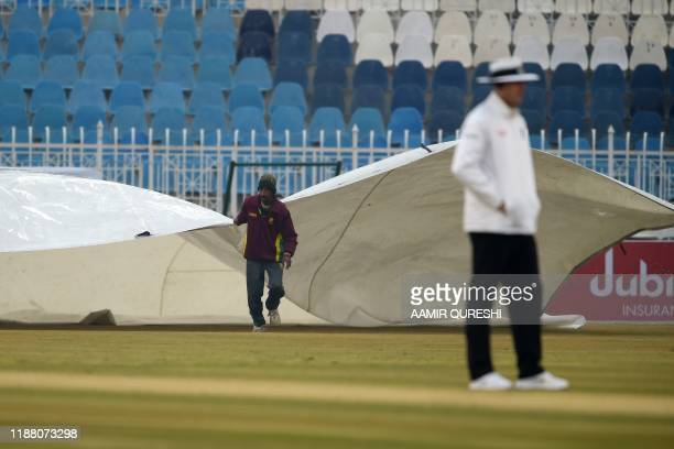 A ground staff member covers the pitch during rain showers on the second day of the first Test cricket match between Pakistan and Sri Lanka at the...