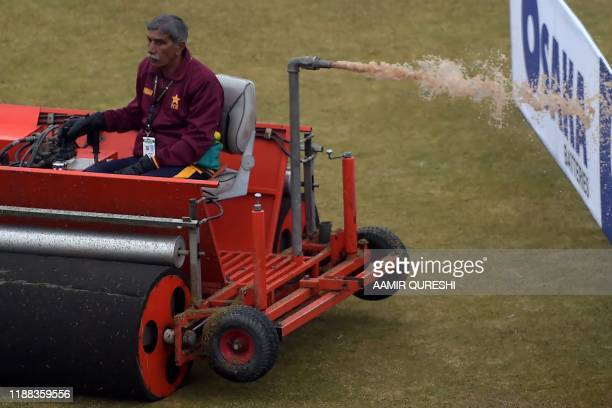 A ground staff member empties the tank of a machine used to soak up water from pitch covers following overnight rain during the fourth day of the...