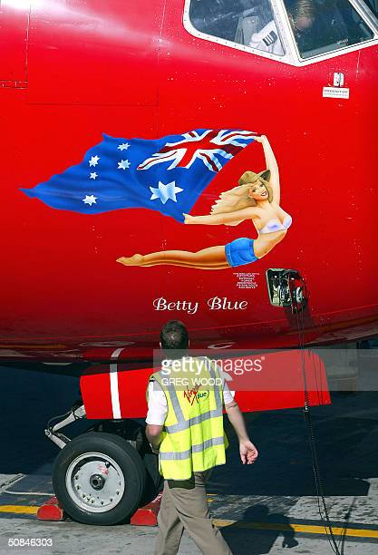 A ground staff member walks past a passenger jet from Australian budget airline Virgin Blue as it is prepared for a flight at Sydney Airport 17 May...