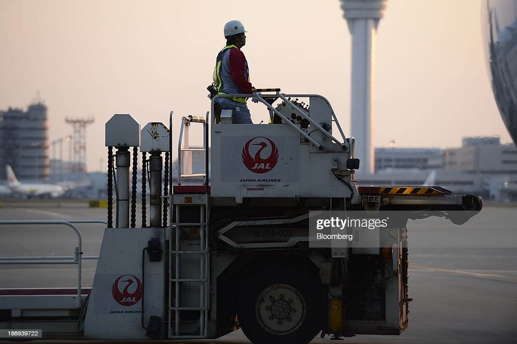 A ground staff member works near a Japan Airlines Co. (JAL) aircraft at Haneda Airport in Tokyo, Japan, on Tuesday, Nov. 5, 2013. JAL, Japan's second-largest carrier, raised its full-year profit outlook on Oct. 31 as it expects demand to increase on its Southeast Asia routes. Photographer: Akio Kon/Bloomberg via Getty Images