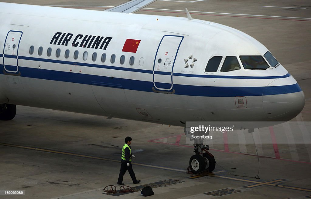 A ground staff member works towards an Air China Ltd. aircraft at Shanghai Pudong International Airport in Shanghai, China, on Saturday, Oct. 26, 2013. Airline profits worldwide in 2013 will be 7.9 percent smaller than estimated at $11.7 billion amid sluggish travel demand and rising oil prices tied to the Syria crisis, the International Air Transport Association said last month. Photographer: Tomohiro Ohsumi/Bloomberg via Getty Images