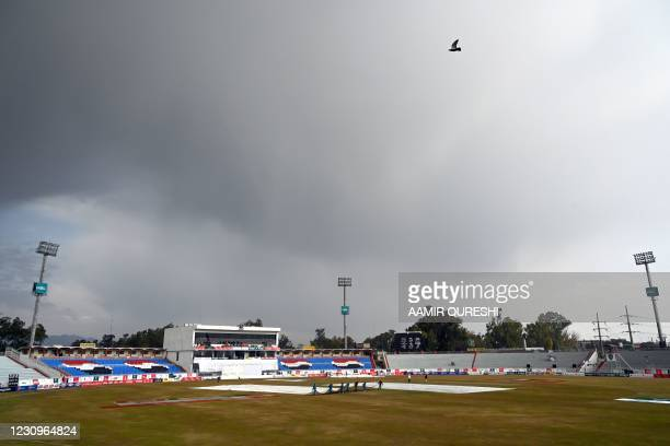 Ground staff members cover the pitch following rain showers as the 3rd session is delayed during the first day of the second Test cricket match of a...